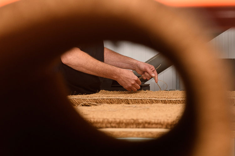 Hand Stitching a Coir Mat in our workshop
